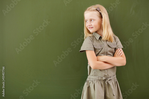 Scoolgirl standing near blackboard