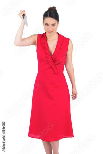 Frightening elegant brunette in red dress holding knife
