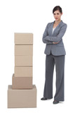 Confident businesswoman with cardboard boxes