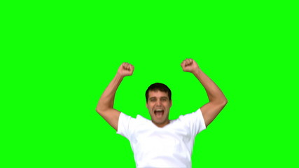 Cheerful man raising arms on green screen