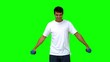 Attractive man lifting dumbbells on green screen