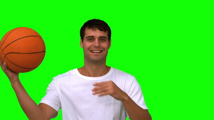 Man playing with a basketball on green screen