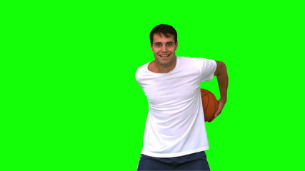Man playing and dribbling with a basketball on green screen