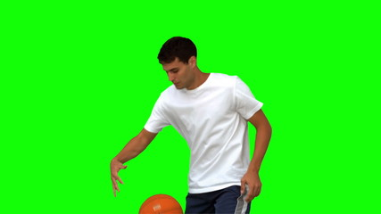 Man dribbling with a basketball on green screen