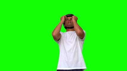 Man wearing a helmet holding his head on green screen