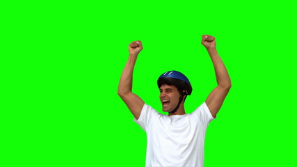 Man on his bicycle raising arms on green screen