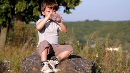 Boy drinkin mineral water from plastic bottle