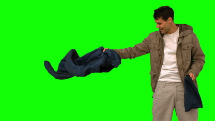 Man rolling out his sleeping bag on green screen