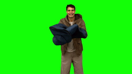Cheerful man rolling out his sleeping bag on green screen