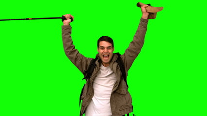 Cheerful man raising his hat on green screen