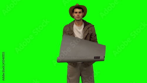 Man rolling out a sleeping bag on green screen