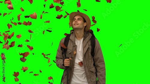 Man standing under leaves falling on green screen