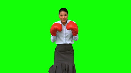 Businesswoman wearing boxing gloves and hitting on green screen