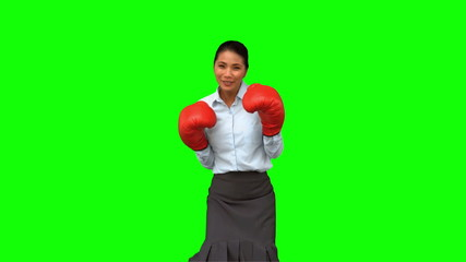 Businesswoman with boxing gloves hitting on green screen