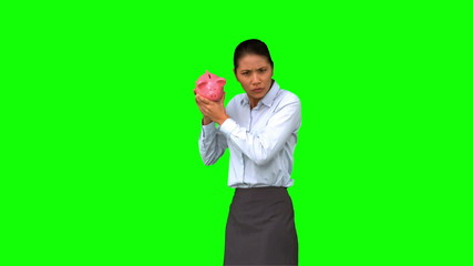 Businesswoman shaking an empty piggy bank on green screen