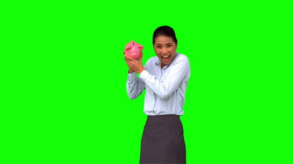 Businesswoman shaking a full piggy bank on green screen