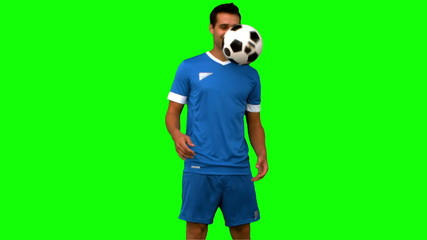 Man juggling a football on green screen