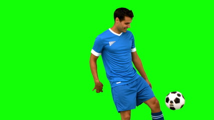 Handsome man juggling a football on green screen
