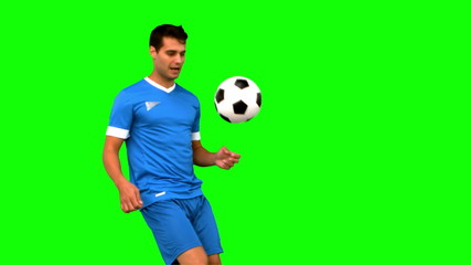 Attractive man juggling a football on green screen