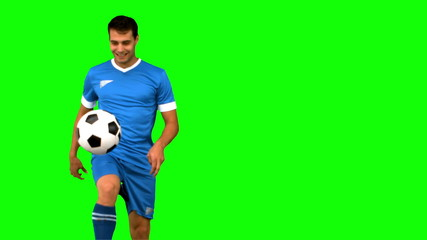 Man playing with a football on green screen