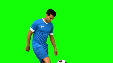 Handsome man playing with a football on green screen