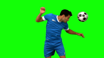 Man heading a football on green screen