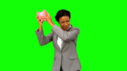 Businesswoman listening to an empty piggy bank on green screen