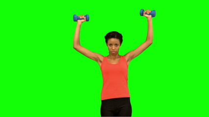 Woman lifting dumbbells on green screen