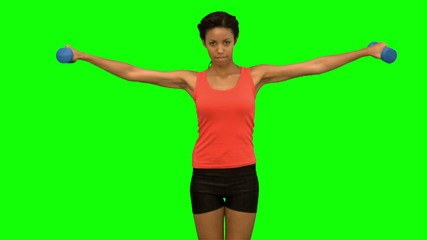 Pretty woman lifting dumbbells on green screen
