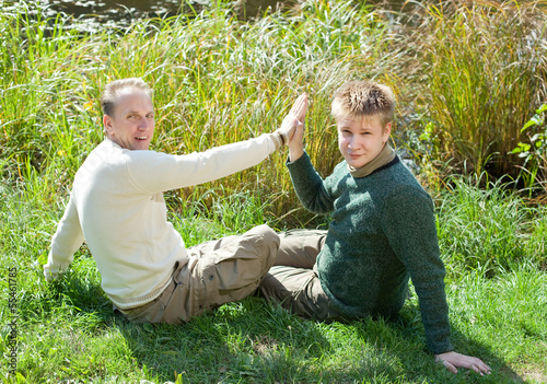 The father with the son sit on the grassy coast of the lake..