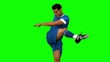 Football player kicking a football on green screen