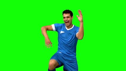 Football player celebrating a goal on green screen