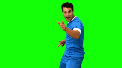 Happy football player celebrating a goal on green screen