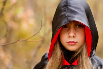 Autumn portrait of a girl in a red and black cloak