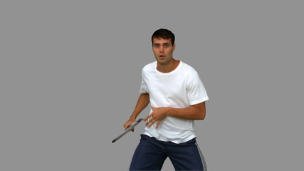 Man training while playing tennis on grey screen