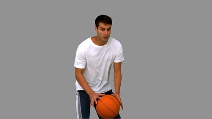 Handsome man playing with a basketball on grey screen