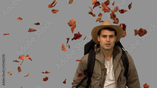 Man with a hat walking under leaves falling on grey screen