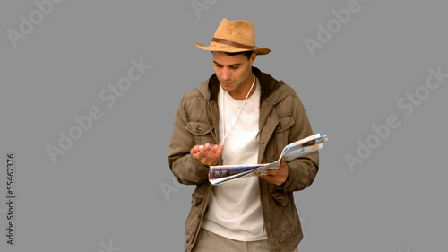 Man with a map and a compass orienteering on grey screen