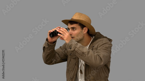 Man wearing a coat using binoculars on grey screen