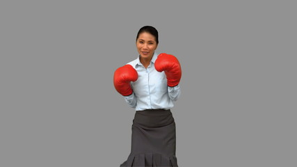 Businesswoman with boxing gloves hitting on grey screen