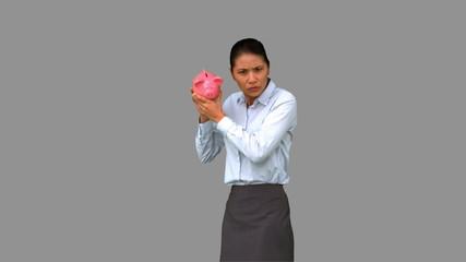 Businesswoman shaking an empty piggy bank on grey screen