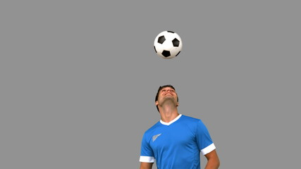 Man juggling a football with his head on grey screen