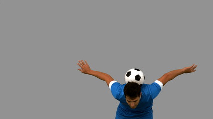 Man juggling a football with head on grey screen
