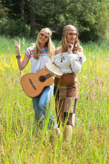 Two retro blonde 70s hippie girls with sunglasses making music w