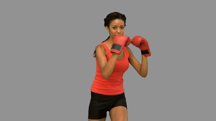 Woman boxing on grey screen
