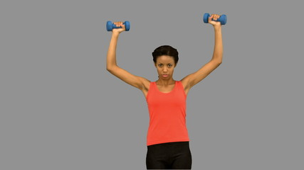 Woman lifting dumbbells on grey screen