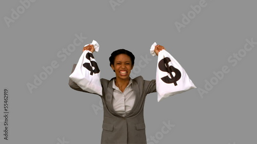 Businesswoman holding money bags on grey screen