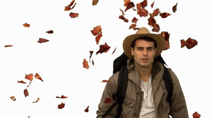 Man with a hat walking under leaves falling on white screen