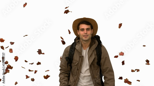 Man walking under leaves falling on white screen