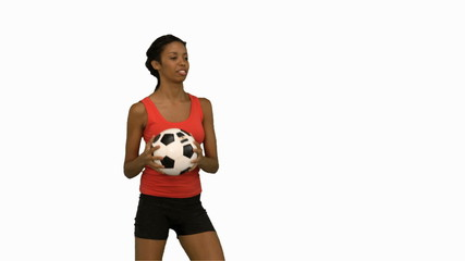 Woman juggling a football on white screen